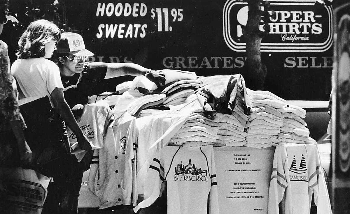 A sweatshirt stand sells clothing to cold tourists along Fisherman's Wharf. June 18, 1986.