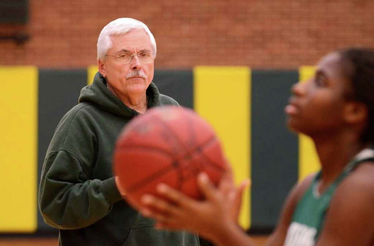 Trinity Catholic's head girls basketball coach, Tom Kriz, watches as Nat Senoble shoots during girls basketball practice at Trinity Catholic High School on Newfield Avenue in Stamford on Tuesday, Dec. 6, 2011.