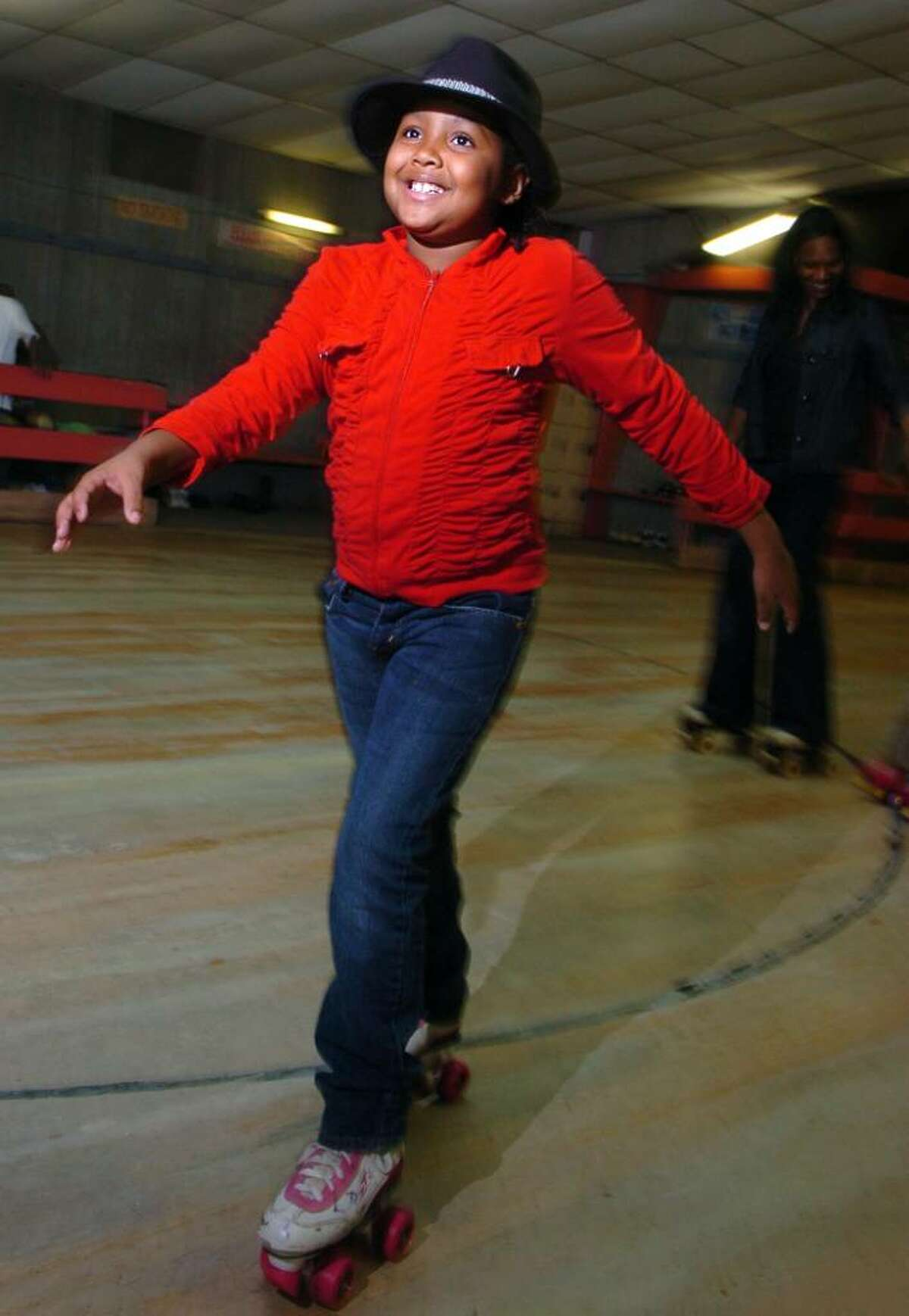 Eight-year-old Talia McBride, of Bridgeport, wears her Michael Jackson hat as she roller skates during
