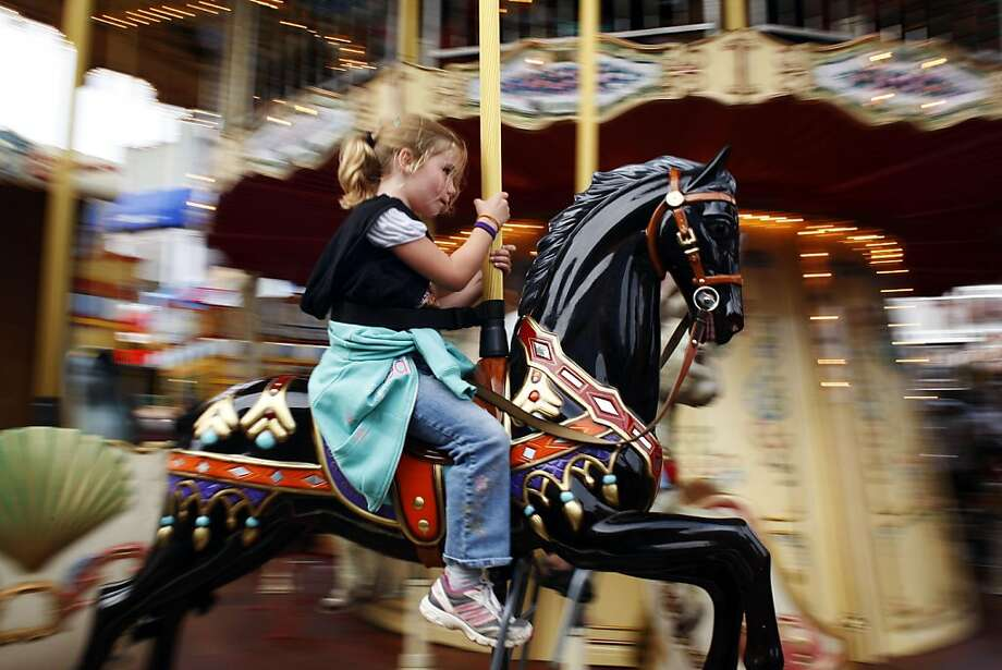 Kaitlyn Ribera, 6, rides the merry-go-round at Pier 39 on Monday, July 18, 2011. Pier 39 is a popular hangout for tourists and San Franciscans alike. Photo: Maddie McGarvey, The Chronicle