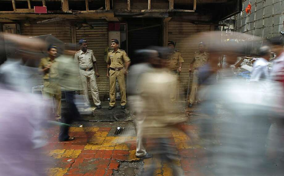 Policemen stand guard as commuters walk by the lane that witnessed a bomb explosion Wednesday, as it is opened for public after police investigation at Zaveri Bazaar, in Mumbai, India, Friday, July 15, 2011. Investigators were examining forensic evidenceand footage from closed circuit cameras Friday for clues about who orchestrated the triple bomb blasts that shook India's business hub of Mumbai and killed 17. Photo: Saurabh Das, AP