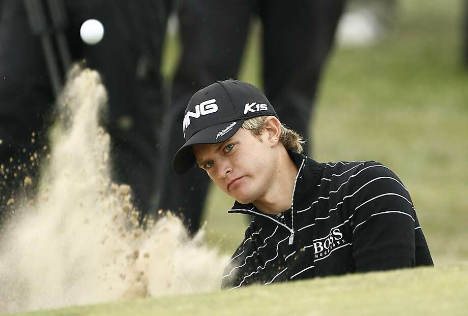 England's Tom Lewis hits a shot out of the bunker on the 11th hole during the first day of the British Open Golf Championship at Royal St George's golf course Sandwich, England, Thursday, July 14, 2011. Photo: Jon Super, AP