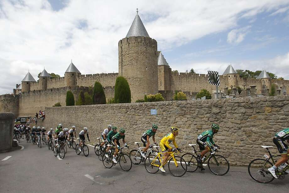 The pack with Thomas Voeckler of France, wearing the overall leader's yellow jersey, pass the historic fortified city of Carcassonne during the 15th stage of the Tour de France cycling race over 193 kilometers (120 miles) starting in Limoux and finishingin Montpellier, southern France, Sunday July 17, 2011. Photo: Christophe Ena, AP