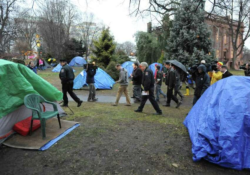 A code inspector from the city walks through Academy Park to see if Occupy Albany has remedied the numerous code violations found Friday on Tuesday, Dec. 6, 2011 in Albany, N.Y. (Lori Van Buren / Times Union)