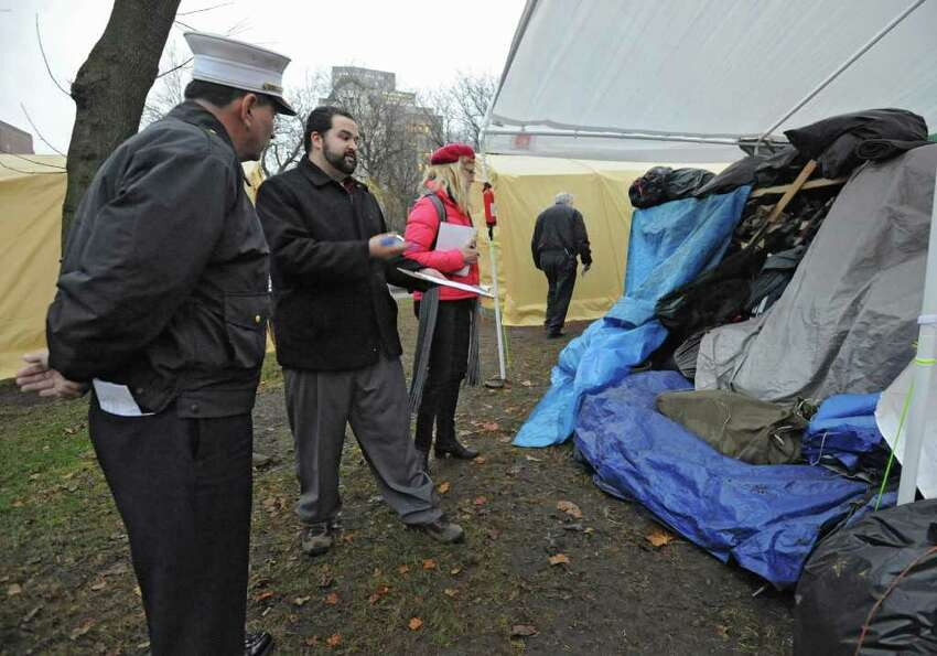 From left, Chief Robert Forezzi talks with Occupy Albany member Daniel Robins as he walks through Academy Park to see if Occupy Albany has remedied the numerous code violations found Friday on Tuesday, Dec. 6, 2011 in Albany, N.Y. (Lori Van Buren / Times Union)