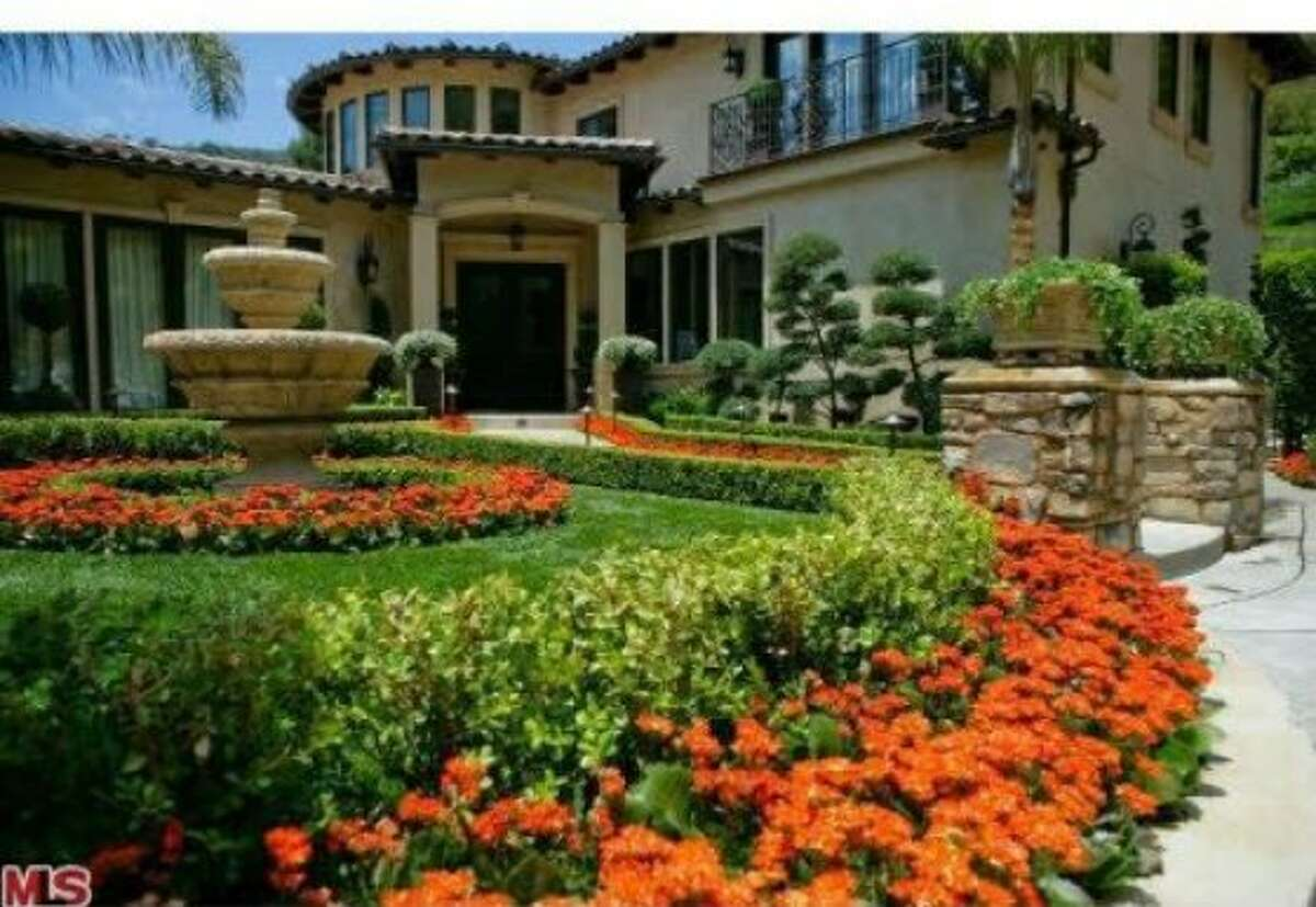 The front yard of the home features beautifully landscaped flowers as well as an intricately designed stone fountain.