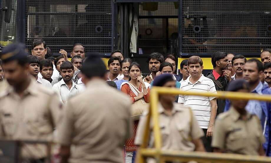 Security personnel stand guard as people crowd near the site of an explosion at Dadar in Mumbai, India, Thursday, July 14, 2011. No terror group has claimed responsibility for the triple bombings that killed 17 people in India's financial capital, and investigators had no immediate suspects in the attacks that came without warning, the country's top security official said Thursday. Photo: Rajanish Kakade, AP