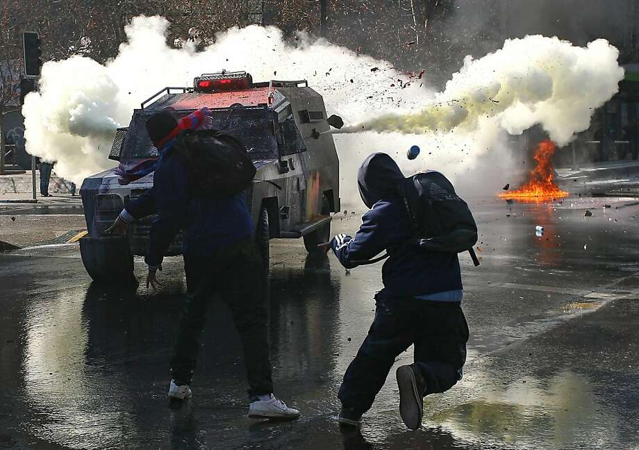 Students throw stones to a riot police tear gas truck during a protest against the government of President Sebastian Pinera and a new education law, in Santiago on July 14, 2011.  Thursday, July 14, 2011 (1800) - TOPSHOTS/ Photo: Hector Retamal, AFP/Getty Images