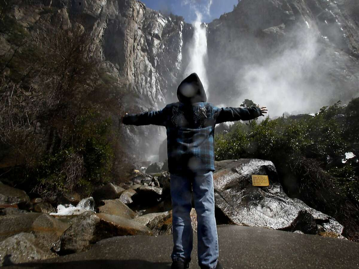At Bridalveil Fall, a young visitor enjoys the cool spray from the water Sunday April 3, 2011. Yosemite has been blessed with a record snow pack for 2011 and the waterfalls that line the valley should be spectacular this spring.