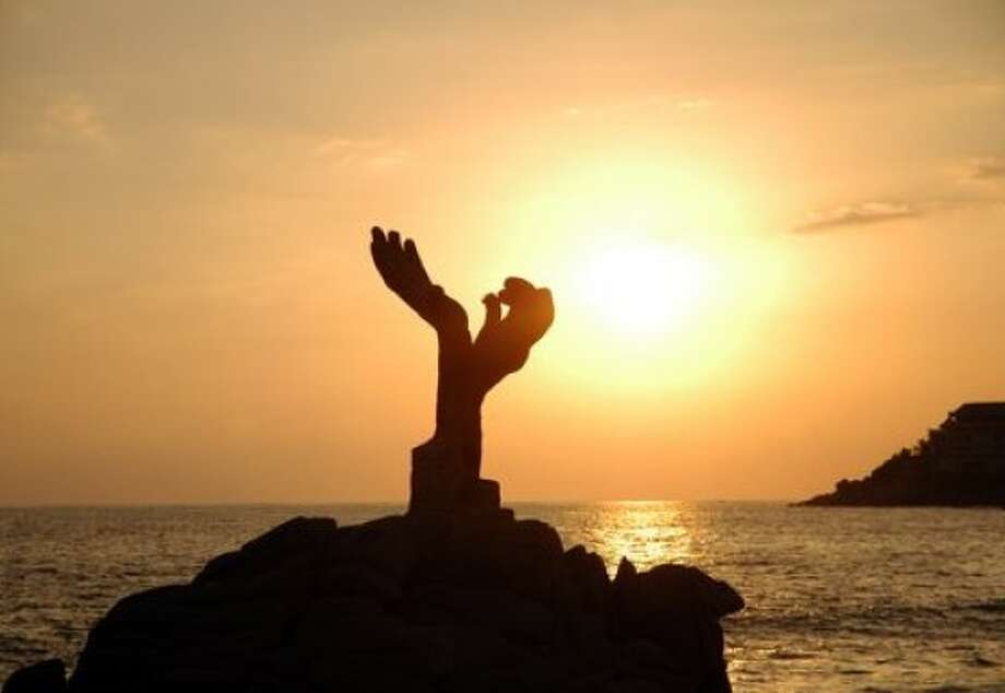 The sunset silhouettes a monument on the beach at Puerto Escondido, Mexico. Photo: Haak78, Shutterstock