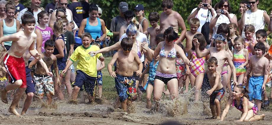 WESTLAND, MI - JULY 12:  Children run into a giant lake of mud during Wayne County's 2011 Mud Day event at Nankin Mills Park July 12, 2011 in Westland, Michigan. The annual event consists of 20,000 gallons of water mixed with 200 tons of topsoil. Photo: Bill Pugliano, Getty Images