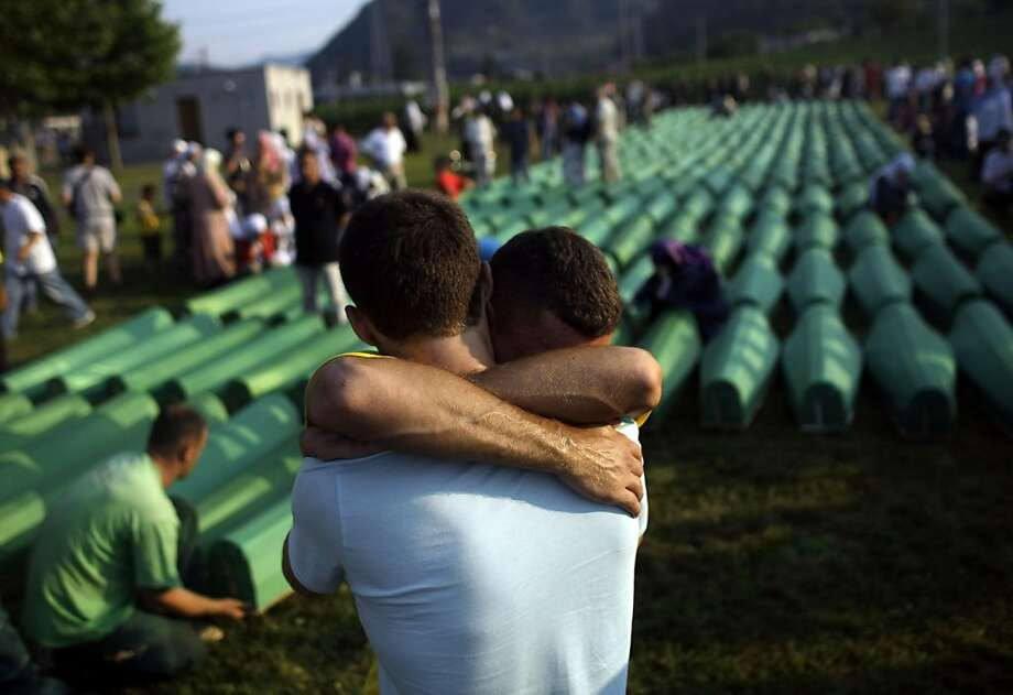 Two men hug each other while mourning in front of over six-hundred coffins displayed at the Potocari memorial cemetery near Srebrenica, some 160 kilometers east of Sarajevo, Bosnia and Herzegovina, Sunday, July 10, 2011. A burial ceremony for the hundredsof victims will be held on Monday, July 11, 2011 in Potocari, on the 16th anniversary of the Srebrenica tragedy when in 1995 Bosnian Serb forces stormed the enclave and systematically killed thousands of Bosnian Muslims. Photo: Marko Drobnjakovic, AP