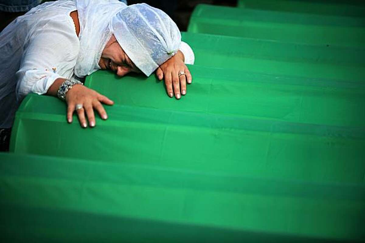 A Bosnian woman mourns over the coffin of a relative during preparations for mass burial at the Potocari memorial cemetery near Srebrenica on July 11, 2010. Tens of thousands on Sunday mark 15 years since the Srebrenica massacre of nearly 8,000 Muslimsby Bosnian Serbs, the darkest episode of the violent break-up of Yugoslavia. TOPSHOTS
