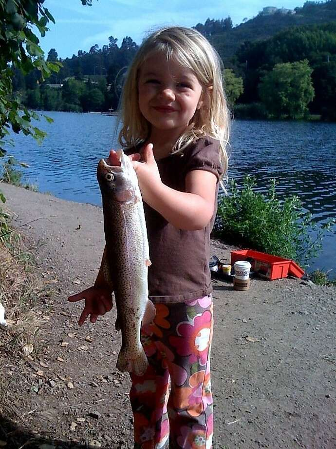 The author's daughter displays a rainbow trout she caught in Oakland's Lake Temescal. Trout and catfish are planted in the lake by both the East Bay Regional Parks District and the California Department of Fish and Game. Photo: Rob Baedeker