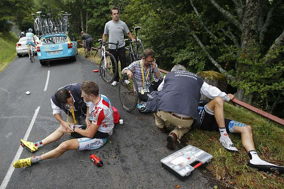Frederik Willems of Belgium, left, and David Zabriskie of the US, right, are being treated by Tour de France doctors after crashing during the 9th stage of the Tour de France cycling race over 208 kilometers (129 miles) starting in Issoire and finishing in Saint Flour, central France, Sunday July 10, 2011. Photo: Christophe Ena, AP