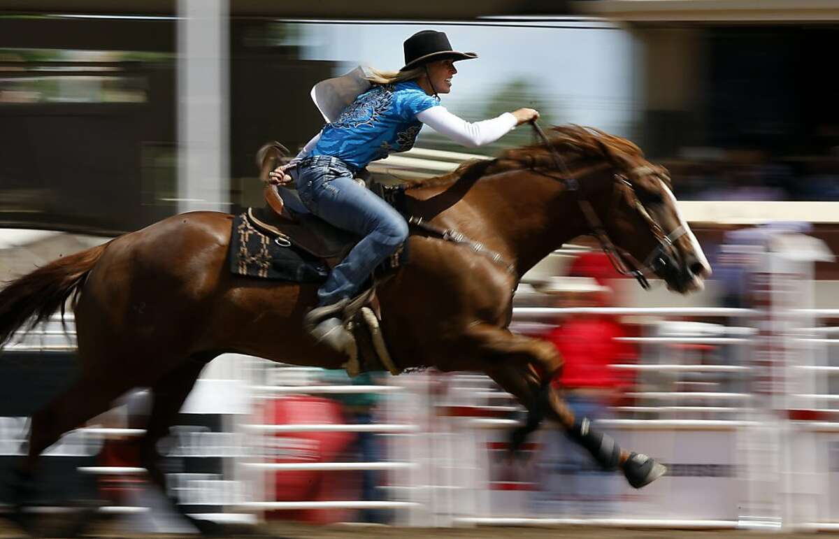 Joleen Seitz, of Canada, competes in the barrel racing event during the rodeo action at the Calgary Stampede in Calgary, Alberta, Sunday, July 10, 2011.