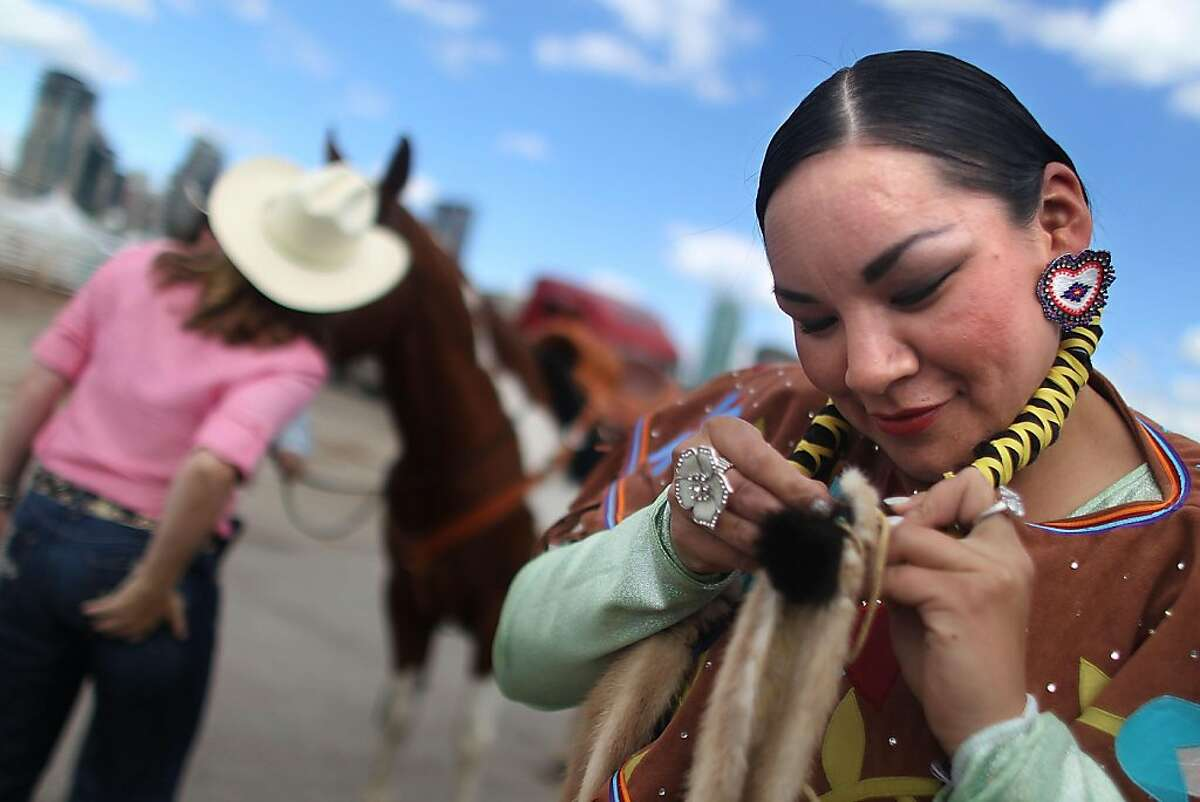 CALGARY, AB - JULY 10: Eva Meguinis from the Tsuu T'ina nation, the 2011 Calgary Stampede Indian Princess, prepares her hair before appearing at the Calgary Stampede on July 10, 2011 in Calgary, Canada. The ten-day event featuring over one million visitors is CanadaÍs largest annual rodeo and is billed as the