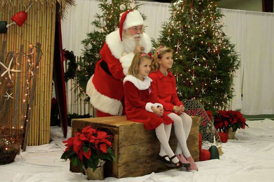 "In this Wednesday, Nov. 30, 2011, Santa, Cliff Snider sneaks up on Tayla Statham, 6, left, and Devon Statham, 8, right, during a Christmas photo shoot at the ""Beach Shack"" in Emerald Isle, N.C. When Snider, who's been playing Santa since he was a teenager, gets a big-ticket request, he typically answers: ""There's an awful lot of children asking for that this year. What else do you want?""    (AP Photo/Tom Copeland) Photo: Tom Copeland"