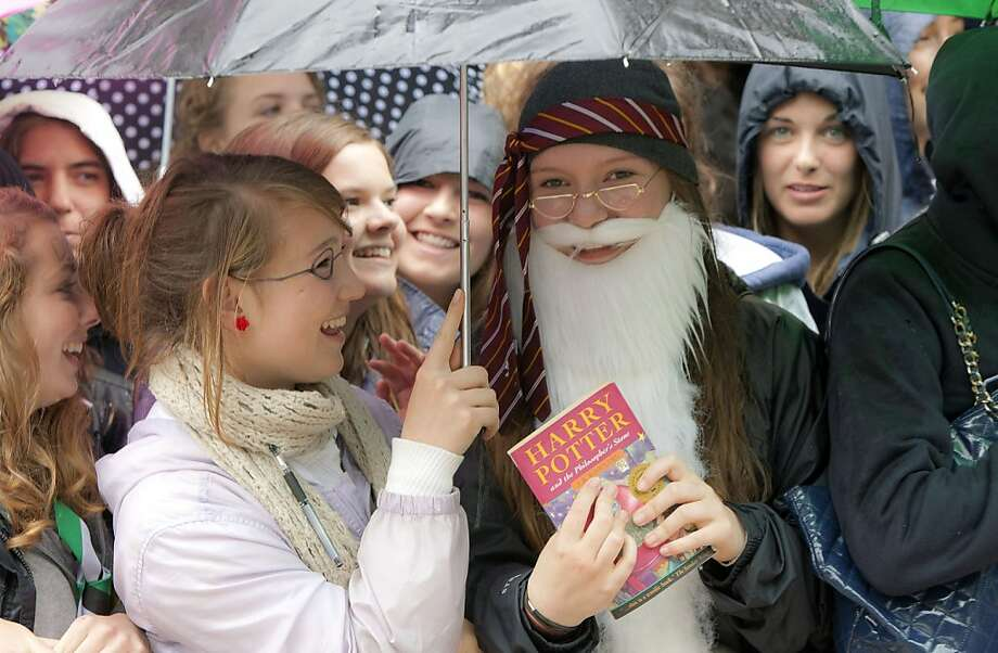 Harry Potter fan Ellie Coote, 15, from Oxford, dressed as Professor Dumbledore clutches a book under an umbrella in the rain outside the cinema in Leicester Square, central London, for the World Premiere of Harry Potter and The Deathly Hallows: Part 2, the last film in the series, Thursday, July 7, 2011. Photo: Joel Ryan, AP