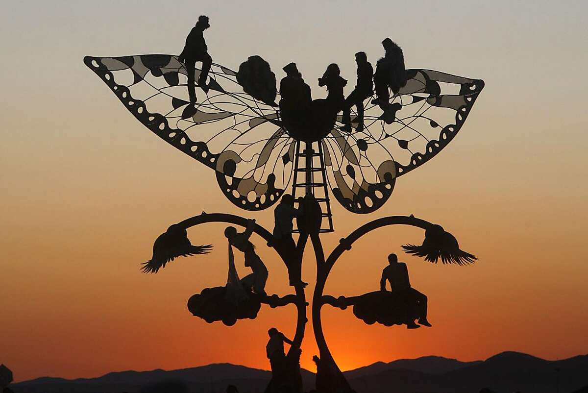 """Burners watch the sunrise over the playa from atop """"Portal of Evolution,"""" a sculpture by Bryan Tedrick. More Burning Man"""
