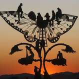 "Burners watch the sunrise over the playa from atop ""Portal of Evolution"" a sculpture by Bryan Tedrick."