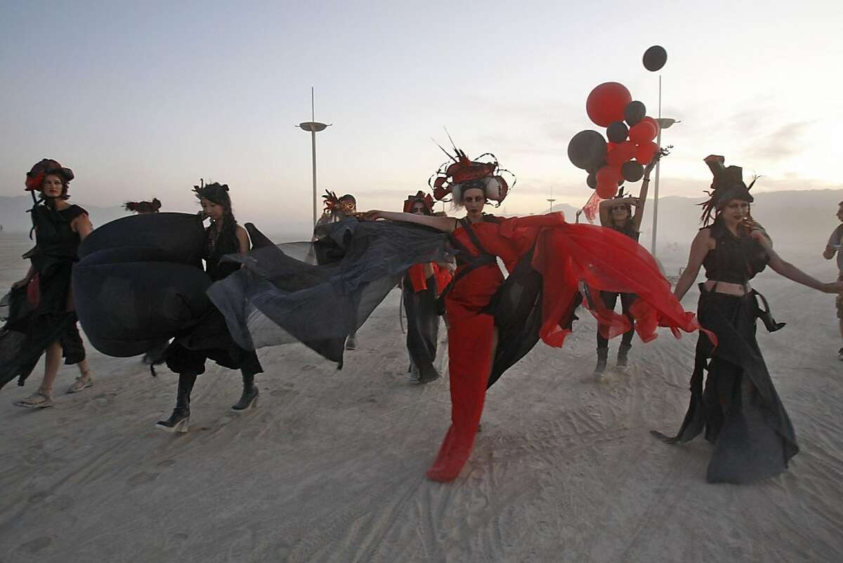 Performing artists dance on the playa during a dust storm at the Burning Man festival in Black Rock City., NV on September 4, 2009.