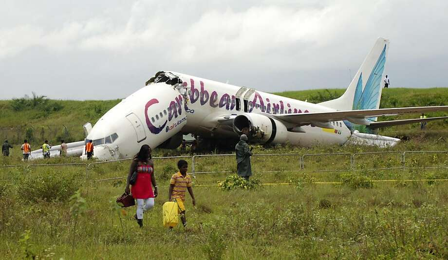 The broken fuselage of a Caribbean Airlines' Boeing 737-800 is seen after it crashed at the end of the runway at Cheddi Jagan International Airport in Timehri, Guyana, Saturday July 30, 2011. The Caribbean Airlines flight 523 from New York touched down onthe rainy runway, slid through a chain-link fence and broke apart just short of a ravine but there were no immediate reports of death among the 163 people aboard, despite several dozen of injuries. Photo: Jules Gibson, AP