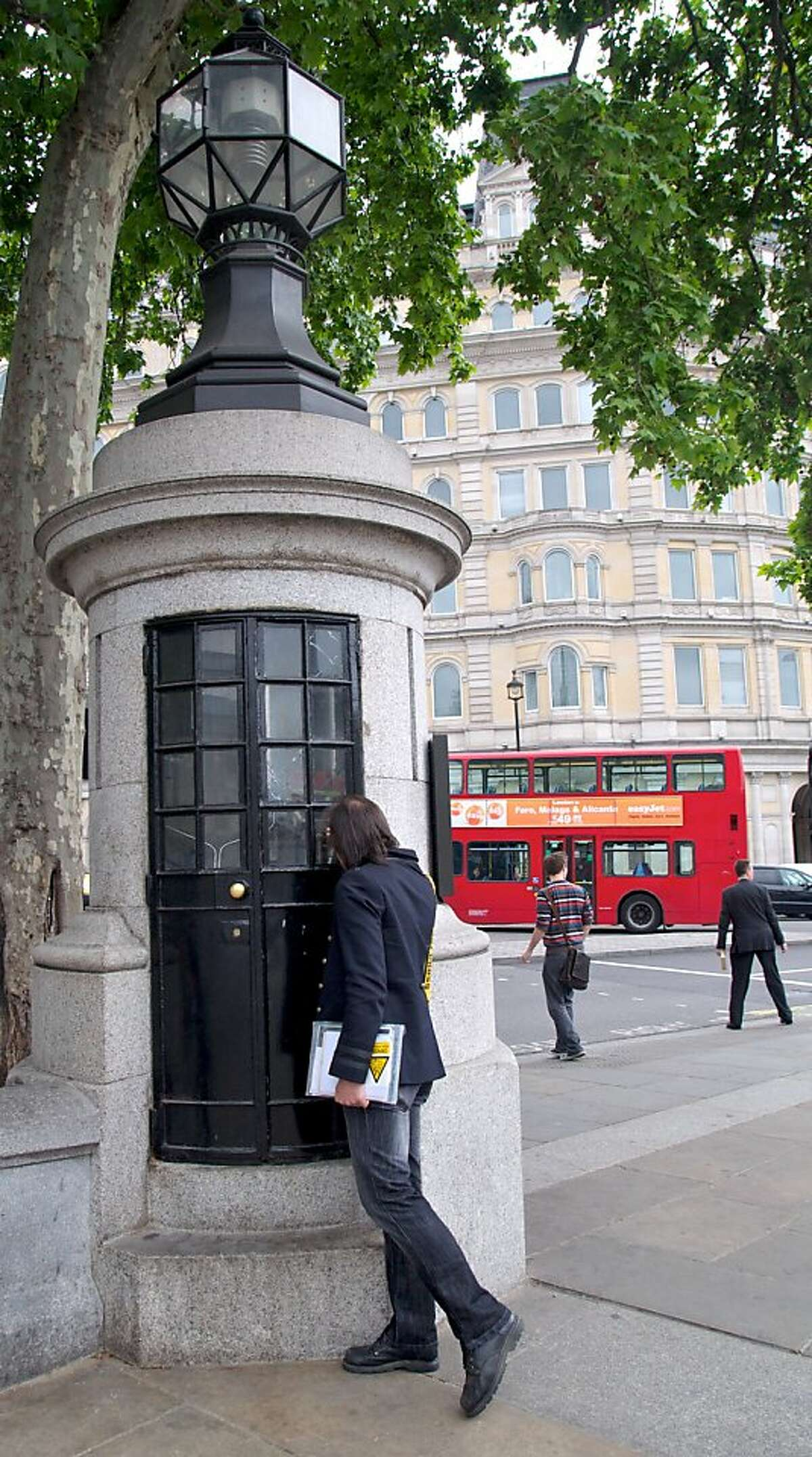 """Tour guide Hedley Allen peers into """"the world's smallest police station"""" at Trafalgar Square in London."""