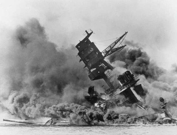 The battleship USS Arizona belches smoke as it topples over after the Japanese surprise attack on Pearl Harbor on December 7, 1941.