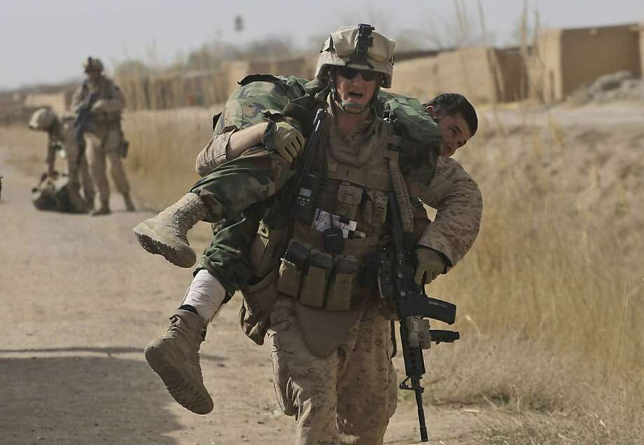 U.S. Marine Lt Scott Holub of Pasadena, MD and from 3rd Battalion, 6th Marine Regiment runs carrying an Afghan National Army soldier who was shot in the lower leg during a battle with the Taliban in Marjah in Afghanistan's Helmand province on Saturday Feb. 20, 2010. Photo: David Guttenfelder, AP