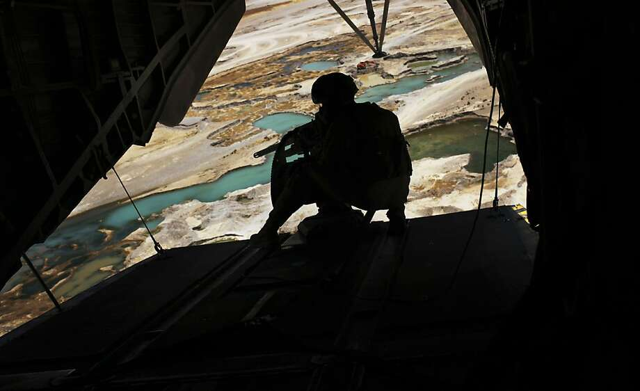 A United States Marine helicopter door gunner holds a heavy machine gun during a flight over Nimroz Province on the border with the volatile Helmand Province in southern Afghanistan, Saturday, July 17, 2010. Photo: Kevin Frayer, AP