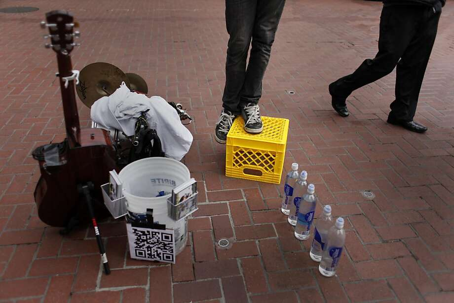 Balancing with one foot atop a plastic milk crate at the cable car turnaround on Powell Street, Jord Peck, 24, prepares to start his show. Photo: Mike Kepka, The Chronicle