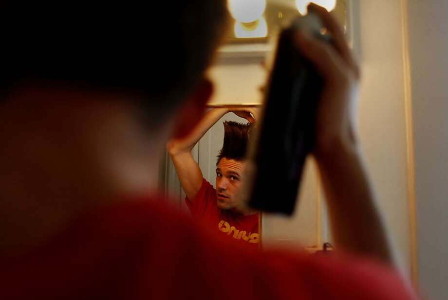 "Jord Peck, 24, puts the finishing touches on his performance hair. ""You can never have enough hairspray,"" said Peck. Photo: Mike Kepka, The Chronicle"