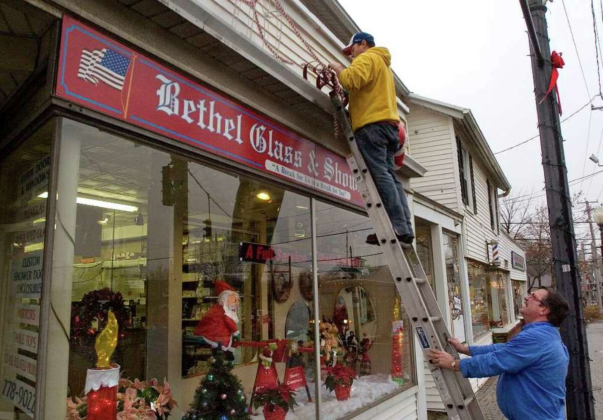Donald Bullock, owner of Bethel Glass & Shower Door, right, holds the ladder for his son, Don Bullock Jr., who is installing Christmas decorations above their display window filled with more holiday ornamentation on Tuesday, Dec. 6, 2011.
