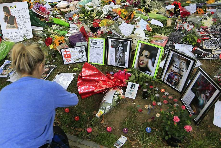 A woman places candles amongst the flowers and tributes left for British singer Amy Winehouse outside her home in London, Tuesday, July 26, 2011. The singer, who had struggled with drug and alcohol abuse for years, was found dead Saturday at home by a member of her security team, who called an ambulance. It arrived too late to save her. Photo: Sang Tan, AP