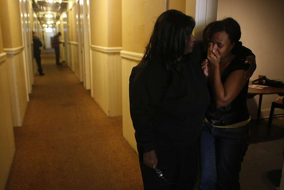"""De De Tillman comforts her tearful daughter Autumn Tillman down the hall from where Santa John Toomey's body was discovered in his room at the Budget Inn in San Francisco Calif., on July 29, 2011. """"This hallway will never be the same without him,"""" said De De Tillman."""