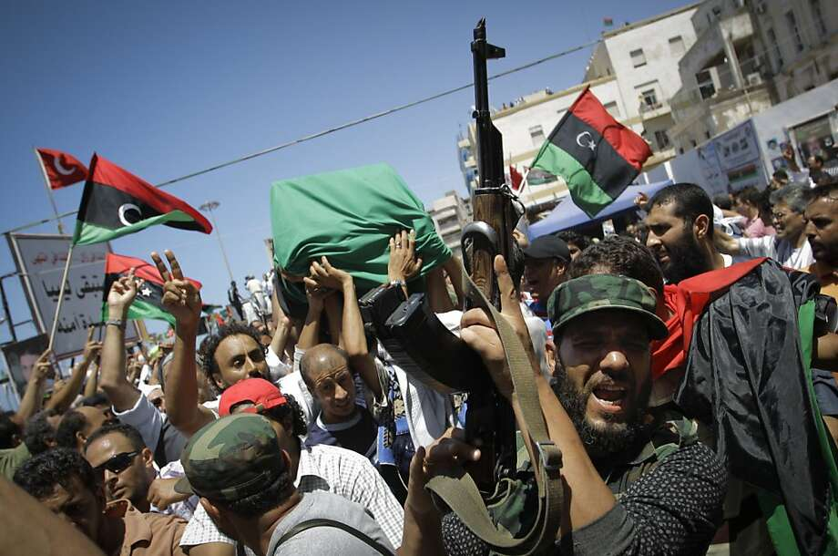 Libyans gesture and chant slogans during a funerals of Libyan rebels' slain military chief Abdel-Fattah Younis in the rebel-held town of Benghazi, Libya, Friday, July 29, 2011.  Thousands of mourners marched in the funeral procession Friday for the Libyanrebels' slain military chief, a day after he was gunned down under still mysterious circumstances. Abdel-Fattah Younis was killed as he traveled from his front lines operations room to the rebels' de facto capital Benghazi. Photo: Sergey Ponomarev, AP