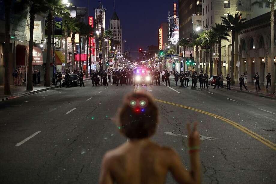 Noel Buller, 21, from Los Angeles, California, stands in the middle of Hollywood Boulevard holding up a peace sign while a line of Los Angeles Poilce Department officers ask the crowd to disperse, following a large, rowdy gathering for a concert by DJ Kaskade on July 27, 2011. Officials are considering charges against event organizers. (Jay L. Clendenin/Los Angeles Times/MCT) Photo: Jay L. Clendenin, MCT