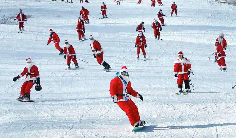 Some of the 250 Santas participating in a fundraising event take a run at Sunday River Ski Resort, S