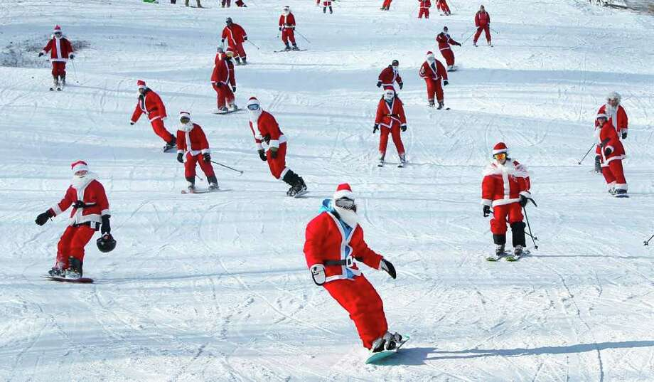 Some of the 250 Santas participating in a fundraising event take a run at Sunday River Ski Resort, Sunday, Dec. 4, 2011, in Newry, Maine. To qualify for a free lift ticket each Santa had to wear a full red Santa costume, complete with beard, and donate at least $10 to the Bethel Rotary Club's annual drive to provide gifts for the area's needy children. Photo: Robert F. Bukaty, Associated Press / AP