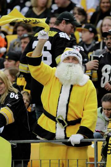 A Pittsburgh Steelers fan dressed in a Black and Gold Santa Claus outfit twirls a Terrible Towel as