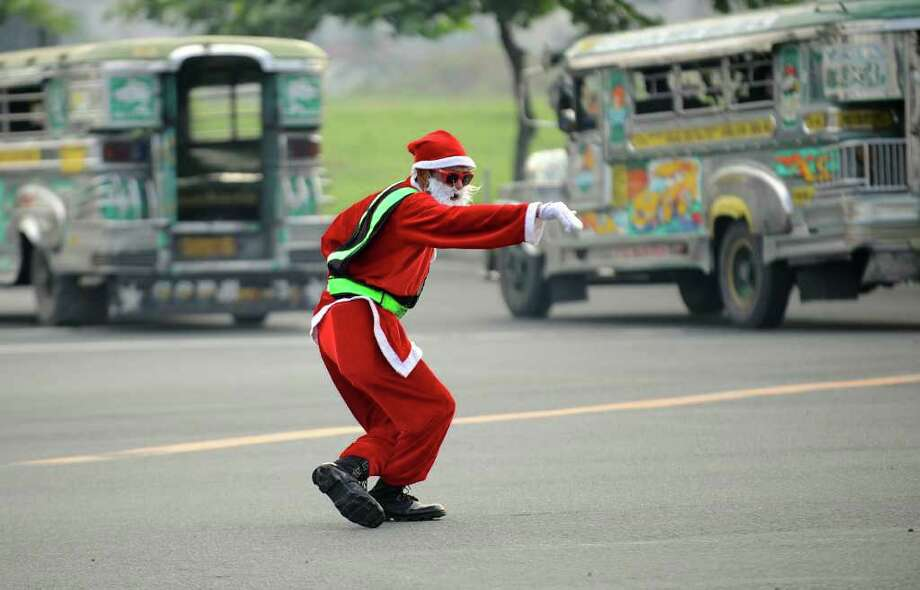 "Philippine traffic enforcer Ramiro Hinojas, wearing a Santa Claus costume, directs traffic along a major road in Manila on December 6, 2011. Popularly known as the ""dancing traffic cop"", the barely five-foot Hinojas, 55, is one of thousands of traffic enforcers who struggle daily to keep Manila's notorious road traffic from moving, despite insults from some impatient motorists and health dangers posed by pollution. Photo: TED ALJIBE, Getty / AFP"