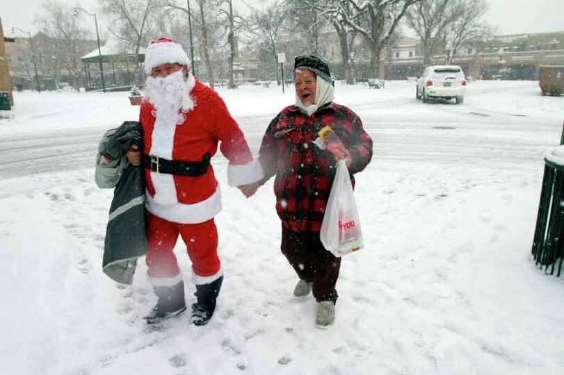 Santa Claus Gilbert Garcia, left, and his mother, Aplonita Montoya visit the Mary Esther Gonzales Se