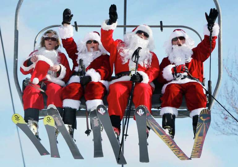 Some of the 250 Santas participating in a fundraising event ride the chairlift at Sunday River Ski R