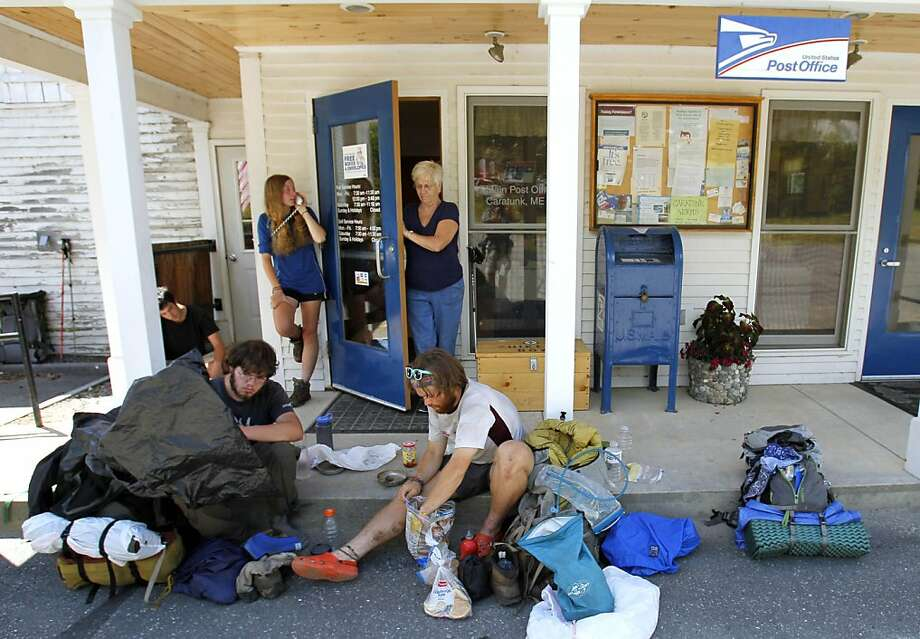 Local Norma Desrochiers makes her way out of the post office where Appalachian Trail thru-hikers Greg Brown, left, and David Hyman, both of Pleasantville, N.Y., sort through their gear, while Madelyn Hoagland-Hanson, of Philadelphia, speaks on the phone,outside the post office in Caratunk, Maine, Thursday, July 28, 2011. The U.S. Postal Service plans to close some rural post offices including some that Appalachian Trail hikers have come to rely on for vital supply drops on their trip from Georgia to Maine. Photo: Robert F. Bukaty, AP