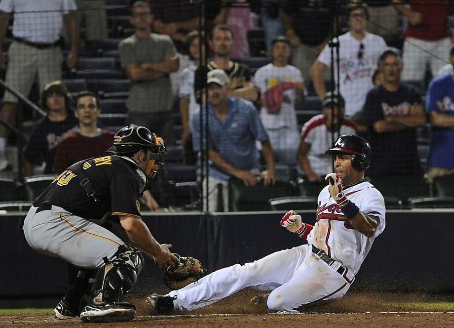 Atlanta Braves' Julio Lugo, right, slides into home plate safely to score the game-winning run as Pittsburgh Pirates catcher Michael McKenry tries to make the tag during the 19th inning of a baseball game, early Wednesday, July 27, 2011. in Atlanta. TheBraves won 3-2. Photo: John Amis, AP