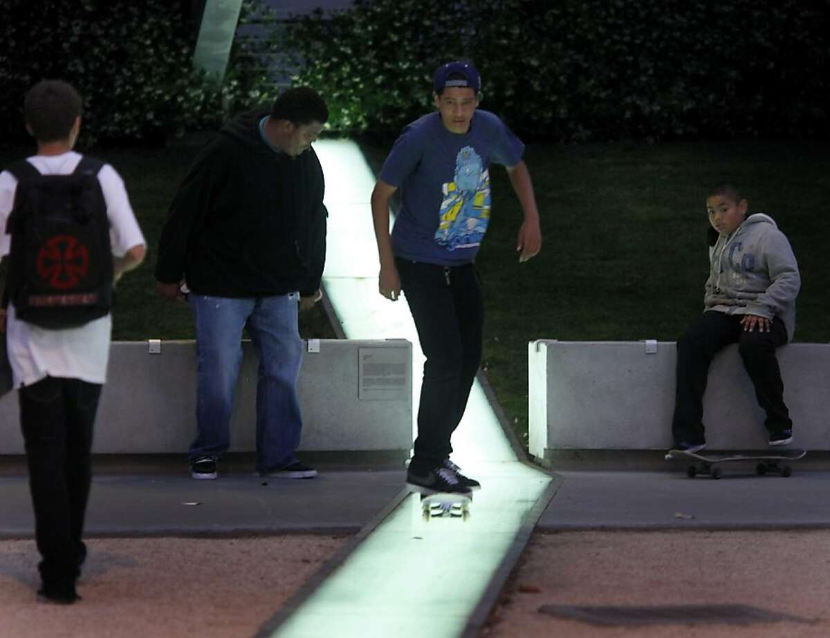 Skateboarders use a smooth lit surface in the plaza to get some speed Monday July 18, 2011. Residents living nearby the new federal building at Seventh and Mission Streets in San Francisco, Calif. say a lack of security in the area has created a lawless haven.