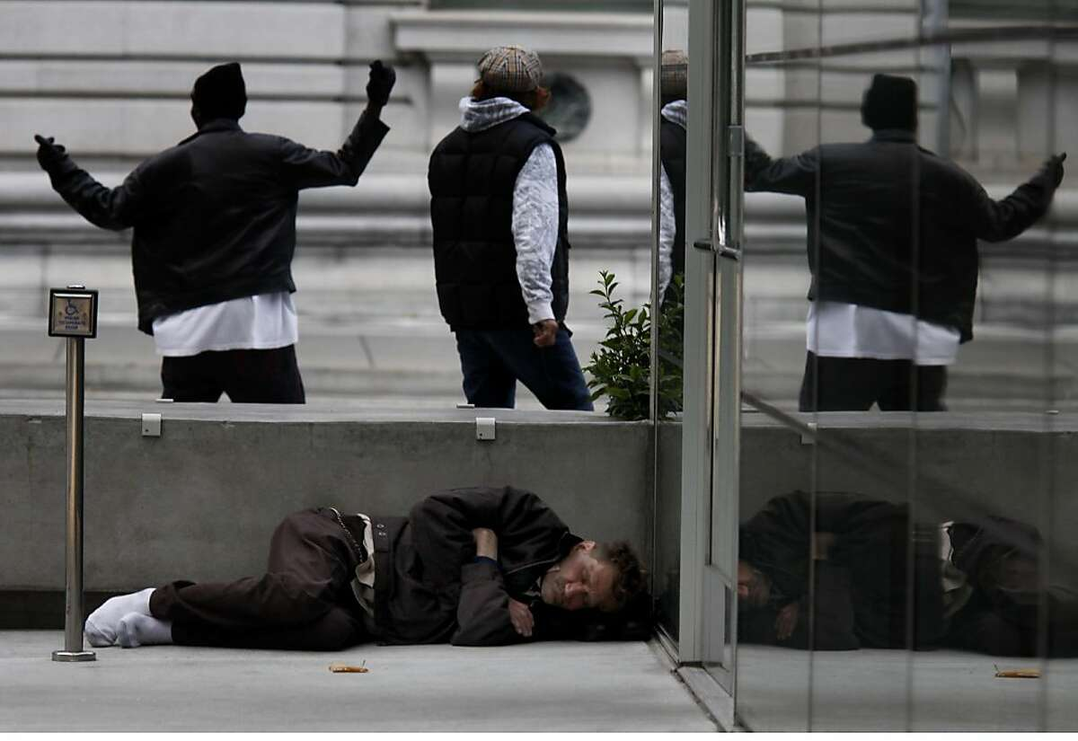A man sleeps behind one of the large cement blocks in the plaza, a favorite hiding place. Residents living nearby the new federal building at Seventh and Mission Streets in San Francisco, Calif. say a lack of security in the area has created a lawless haven.