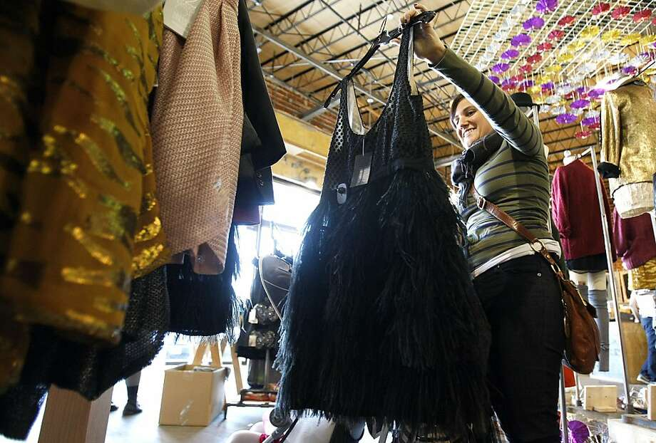 Tracy Flanagan looks at a black feather dress made by Cooperative called Plumage at Urban Outfitters in the Rice Village neighborhood where retro fashions are in style this holiday season Wednesday, Nov. 30, 2011, in Houston.  ( Johnny Hanson / Houston Chronicle )  Ran on: 12-07-2011 Tracy Flanagan looks at a black feather dress made by Cooperative called Plumage at Urban Outfitters in the Houston area. Photo: Johnny Hanson, Houston Chronicle