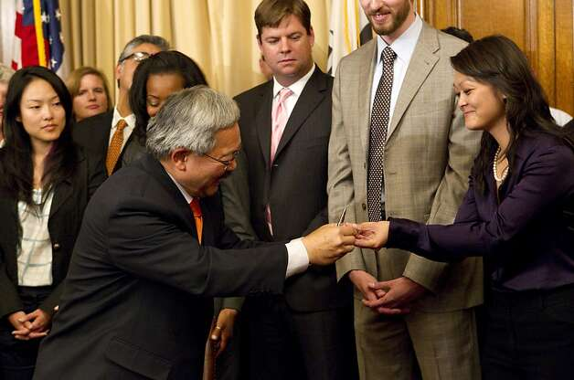 San Francisco Mayor Ed Lee hands one of the pens he used to sign the budget for the 2011-2012 fiscal year to Supervisor Carmen Chu, Chair of the Board's Budget and Finance Committee, after signing the budget during a ceremony at City Hall in San Francisco, Calif., on Tuesday, July 26, 2011. Photo: Laura Morton, Special To The Chronicle